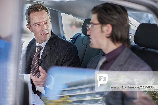 Zwei Geschäftsleute unterhalten sich auf dem Rücksitz eines Autos