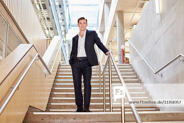 Porträt eines jungen Geschäftsmannes  der auf einer Bürotreppe steht