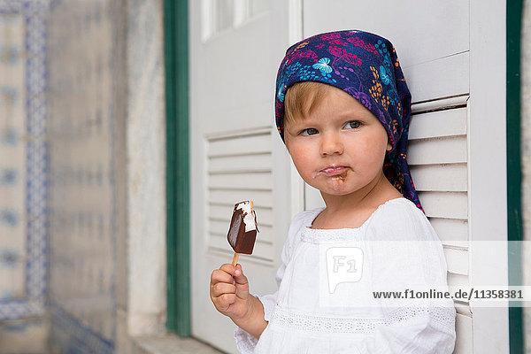 Porträt eines weiblichen Kleinkindes  das sich an Fensterläden lehnt und Eis am Stiel isst  Beja  Portugal