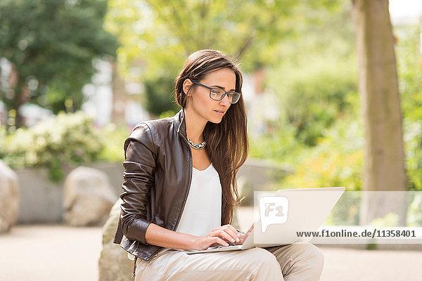 Junge Geschäftsfrau beim Tippen am Laptop im Stadtpark