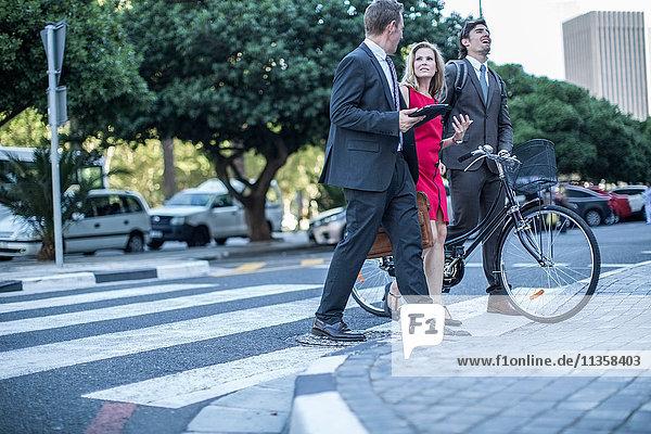 Geschäftsfrau und männliche Kollegen gehen und sprechen in der Stadt