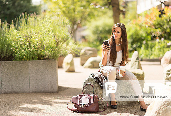 Junge Geschäftsfrau liest Smartphone-Text im Stadtpark