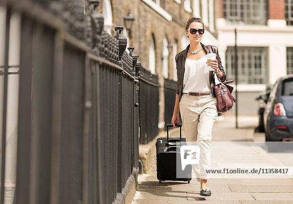 Junge Geschäftsfrau mit Koffer auf Rädern auf der City Street  London  UK