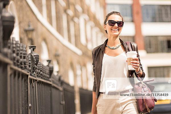 Junge Geschäftsfrau mit Kaffee zum Mitnehmen auf der City Street  London  UK