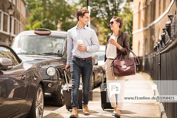 Ein junger Geschäftsmann und eine junge Frau  die mit einem Radkoffer auf der City Street  London  UK  spazieren gehen.