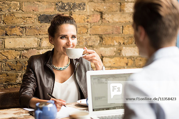 Young businessman and woman drinking tea in cafe