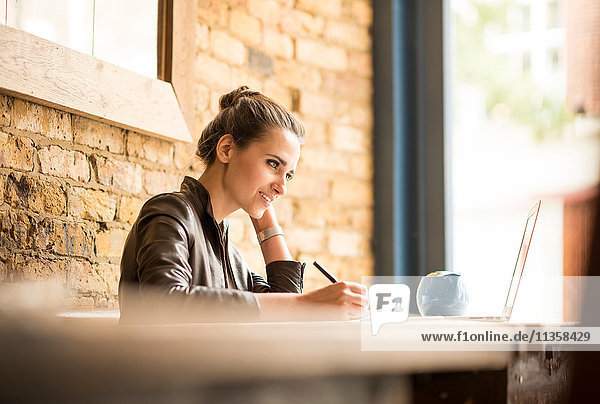 Young businesswoman making notes in cafe