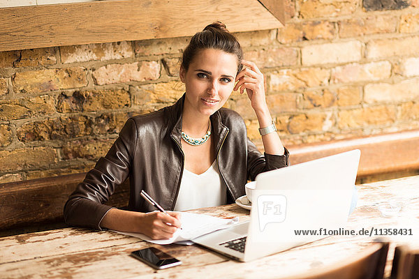 Portrait of young businesswoman making notes in cafe