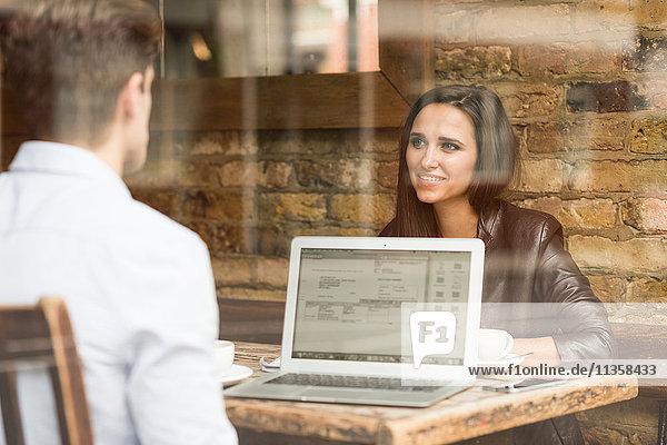 Junge Geschäftsleute  die mit dem Laptop arbeiten und sich im Cafe unterhalten.