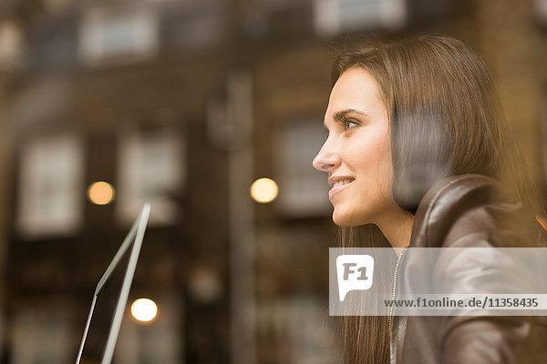 Fensteransicht einer jungen Geschäftsfrau mit Laptop im Cafe
