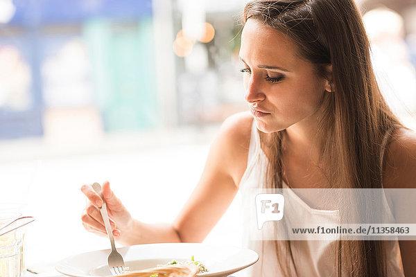 Junge Frau beim Mittagessen im Restaurant