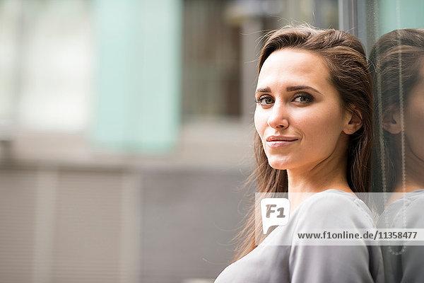 Porträt einer jungen Geschäftsfrau  die sich gegen das Äußere des Büros lehnt  London  UK