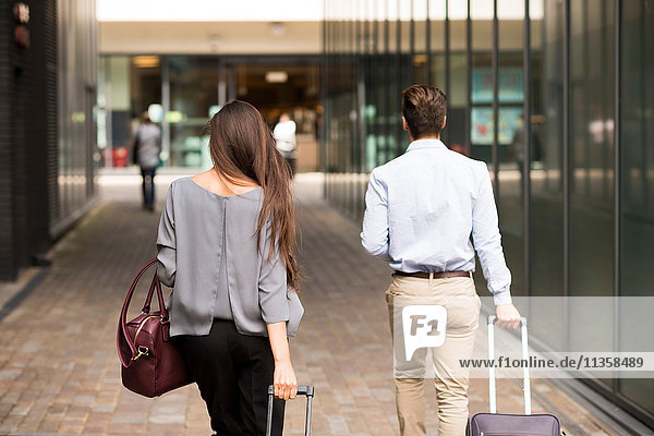 Rear view of young businessman and woman with wheeled suitcases  London  UK
