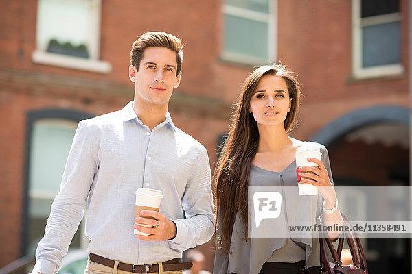 Junger Geschäftsmann und Frau mit Kaffee zum Mitnehmen  London  UK