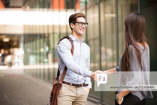 Geschäftsmann und Frau beim Händeschütteln außerhalb des Büros  London  UK