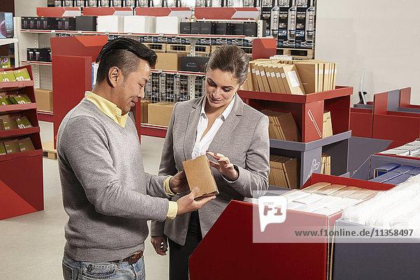 Arbeiter zeigt Produkt vor Manager in Druckerei- und Verpackungsfabrikladen  China