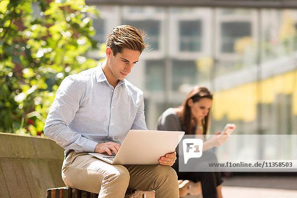 Geschäftsmann beim Tippen am Laptop in der Stadt  London  UK