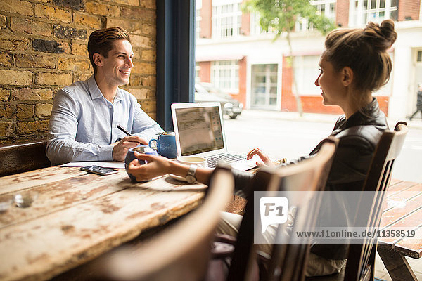 Businessman and woman working in cafe  London  UK