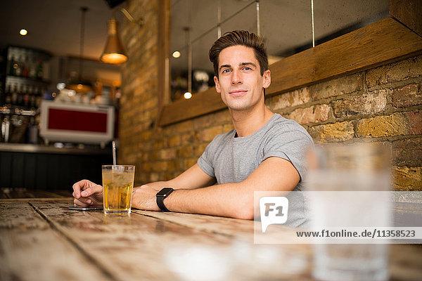 Junger Mann bei Tisch in der Stadtbar