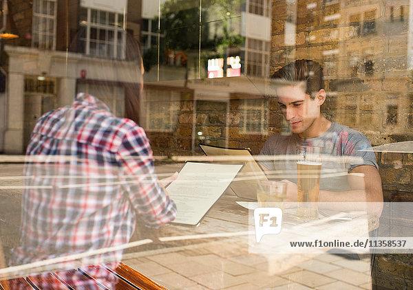 Schaufensteransicht des jungen Paares beim Lesen von Menüs im Restaurant