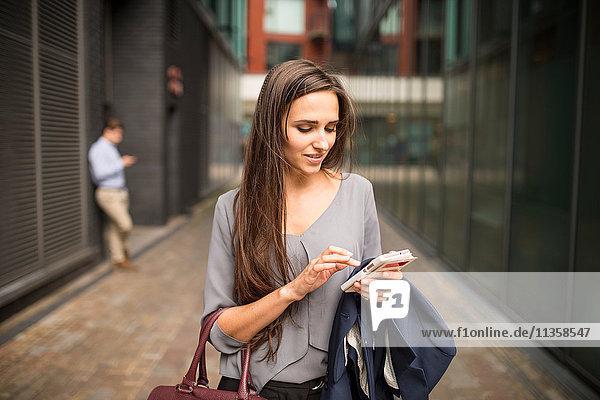 Junge Geschäftsfrau SMS auf Smartphone außerhalb des Büros  London  UK