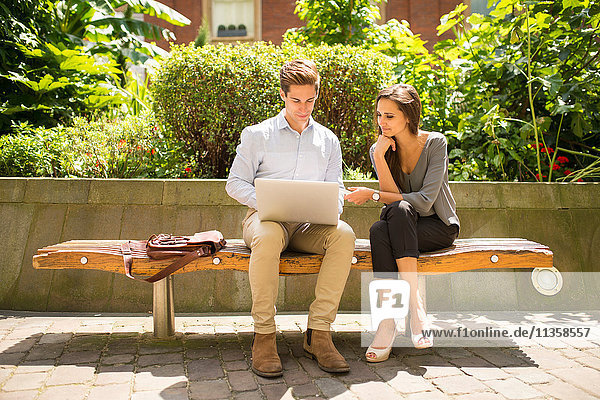 Young businesswoman and man using laptop on bench  London  UK