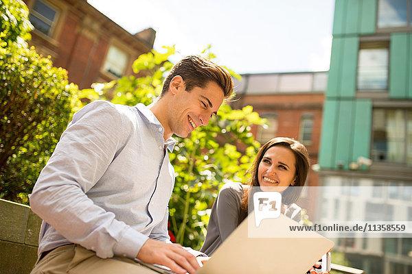 Junge Geschäftsfrau und Mann mit Laptop außerhalb des Büros  London  UK