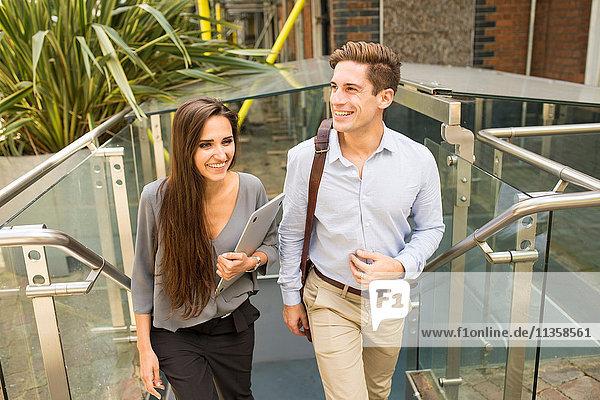 Junge Geschäftsfrau und Mann beim Treppensteigen  London  UK