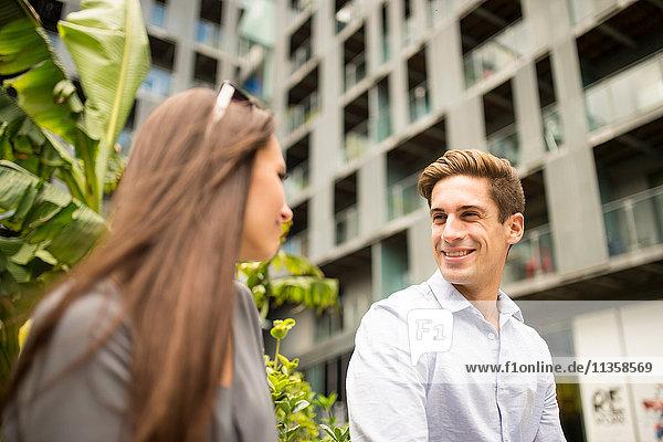 Junge Geschäftsfrau und Mann im Gespräch außerhalb des Büros  London  UK