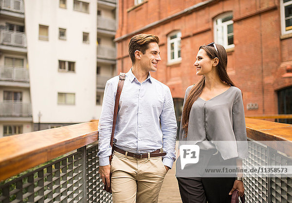 Young businesswoman and man chatting on footbridge  London  UK