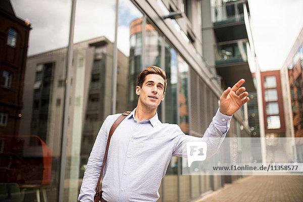 Ein junger Geschäftsmann mit einem Taxi vor dem Büro  London  UK