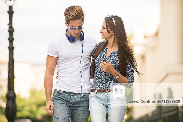 Junges Paar  das durch die Straße schlendert  London  UK