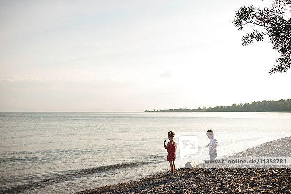 Girl and brother throwing pebbles into Lake Ontario  Oshawa  Canada