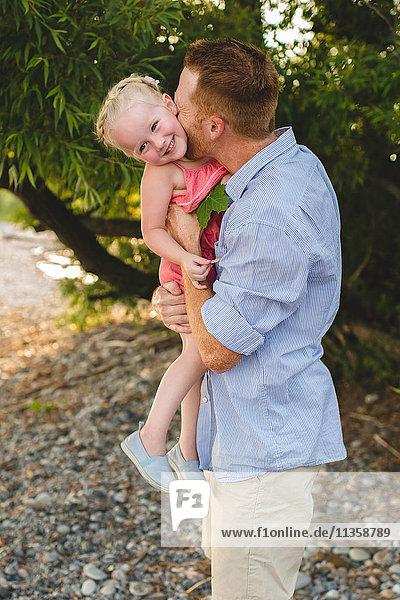 Mid adult man carrying and kissing daughter on cheek at Lake Ontario  Oshawa  Canada