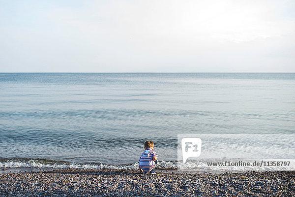 Rear view of small boy crouching and playing at Lake Ontario  Oshawa  Canada