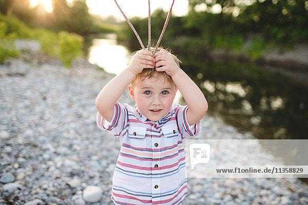 Portrait of cute boy holding sticks on his head at Lake Ontario  Oshawa  Canada