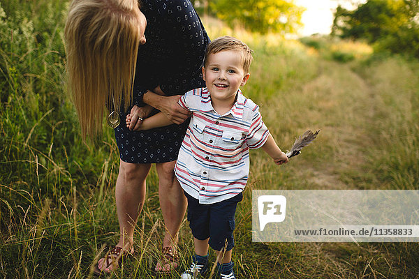 Mother bending down to son with handful of feathers in meadow