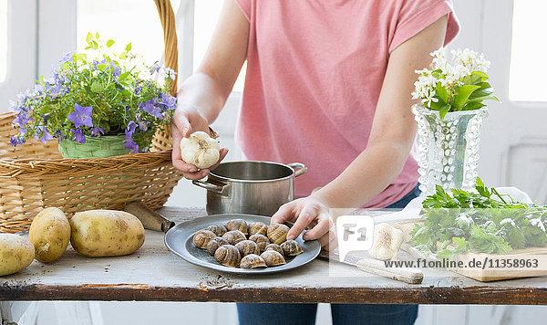 Junge Frau beim Zubereiten von Schnecken und Knoblauch an der Küchentheke  Vogogna  Verbania  Piemont  Italien