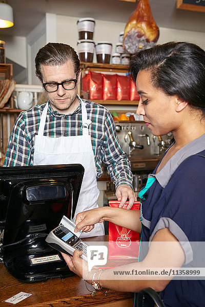Customer in bakery paying for goods  using card machine  mid section