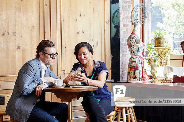 Man and woman sitting in cafe drinking coffee  looking at smartphone