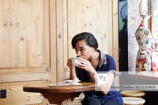 Young woman sitting in cafe  drinking coffee