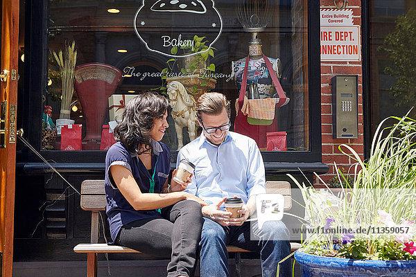 Paar auf Bank sitzend  vor Bäckerei  Kaffeetassen haltend