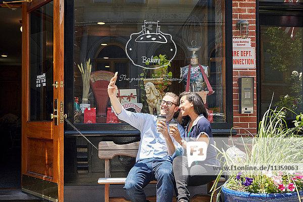 Couple sitting on bench  outside bakery  holding coffee cups  taking selfie with smartphone