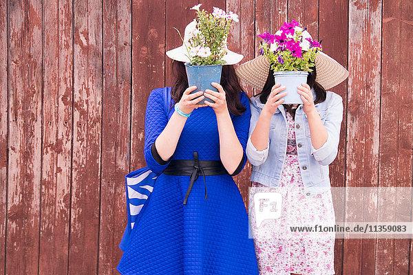 Zwei Frauen mit Sonnenhüten  die Topfpflanzen vor dem Gesicht halten