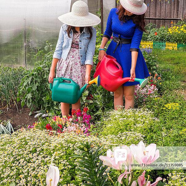 Zwei Frauen mit Sonnenhüten  die mit der Gießkanne Pflanzen gießen