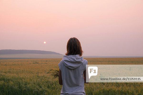 Frau steht im Feld und beobachtet den Sonnenuntergang  Rückansicht  Ural  Russland