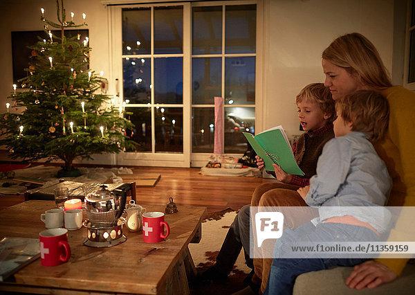 Mutter und Söhne sitzen zu Weihnachten zu Hause und lesen Buch