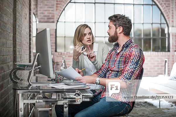 Couple at home  sitting at desk  using computer  having discussion  man holding paperwork