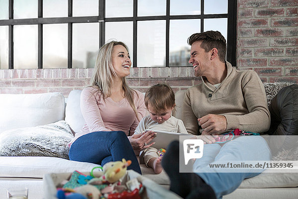 Mutter und Vater sitzen mit Kleinkind auf dem Sofa  Kleinkind hält digitales Tablett