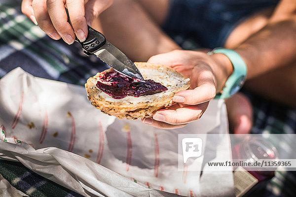 Nahaufnahme einer Frau  die Marmelade auf Saatbrötchen verteilt  Meran  Südtirol  Italien